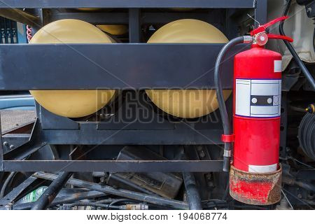 One red tank of fire extinguishers or emergency equipment under the oil tanker truck or gas tanker truck for emergency. Fire extinguishers for truck