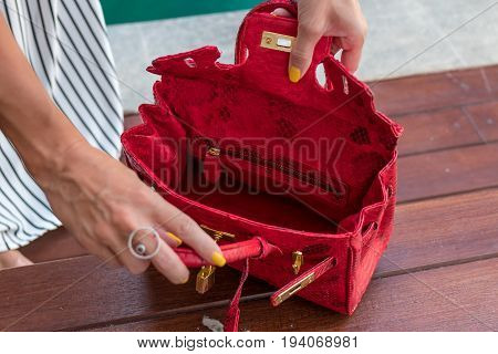 Fashionable woman holding luxury snakeskin python bag. Elegant outfit. Close up of purse in hands of stylish lady. Model posing near the swimming pool.