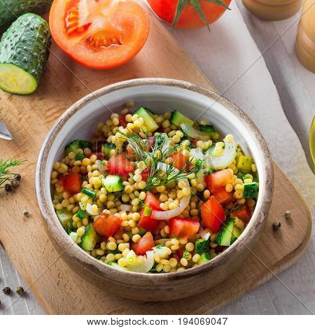Traditional Israeli healthy meal Ptitim with tomatoes cucumber and onion for delicious healthy breakfast. Cooking of classic Moroccan couscous with vegetables. Top view.