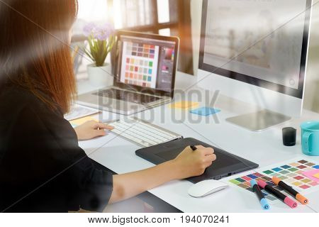 Young asian graphic designer working on computer using digital tablet at office.