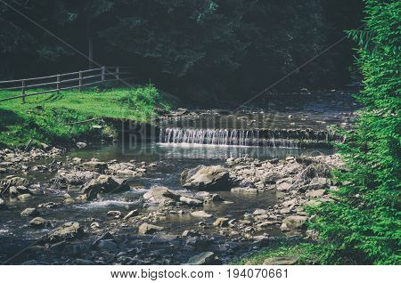 Mountain fast flowing river stream of water in the rocks with fir tree forest in vintage hipster style