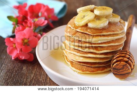 Banana pancakes with honey and caramelized bananas flowering Japanese quince