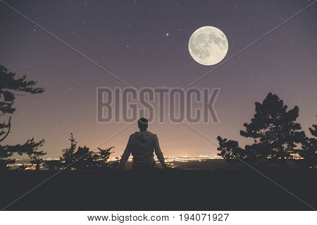 Young man sitting on the wall at night. City lights moon and stars in the background.