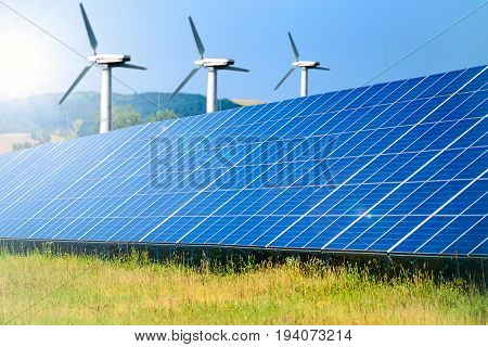 Composite image of renewable energy sources - solar farm for photovoltaic energy and windmills for wind energy