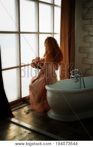 Beautiful red-haired girl romantically sitting on the edge of the bathtub and holding a bouquet. The face is not visible on the background of plants with broad green leaves. In lace dress powdery pastel cream color