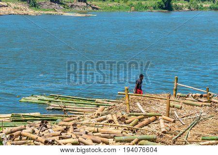 Toamasina Madagascar - December 22 2017: Unidentified Madagascar man is working on bamboo harvesting on the river near the city of Toamasina (Tamatave) Madagascar East Africa. Everyday life on the river.