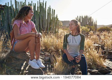 Chatting Girl Friends Sitting On Rocks