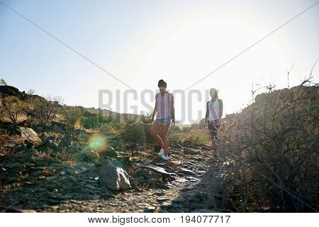 Two Girls Walking A Rocky Pathway