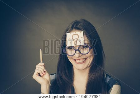 Woman confused thinking seeks a solution paper card with light idea bulb on her head. Excited girl with many ideas celebrating success. Eureka creativity concept