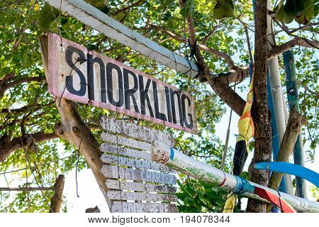 Wooden plate with text snorkling on the Sanur beach, tropical island Bali.