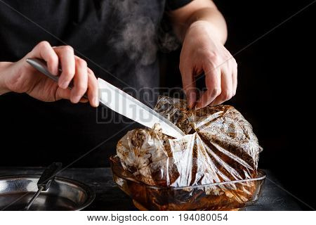 Man takes cooked pieces of marinated pork shoulder from roasting sleeve