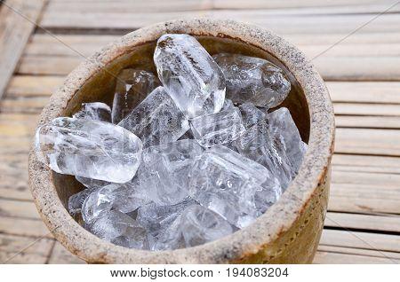 Ice cubes on wooden bucket on Texture background