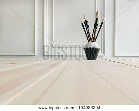 Paint brushes on desk Different paint brushes of bristles in a ceramic vase are standing on a wooden table Photo background for text place copy space