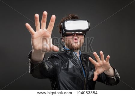 Man in a black leather jacket wearing virtual reality goggles