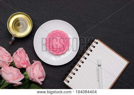 Snow skin mooncake and tea cup with flowers on dark background. Open notebook with copy-space.