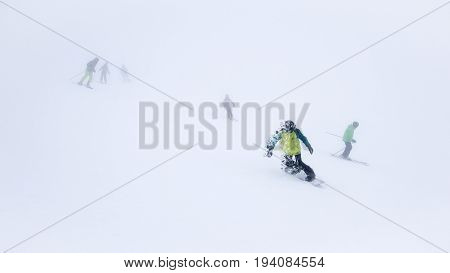 Skiers and snowboarders in thick fog one of them scatter of fume effect.