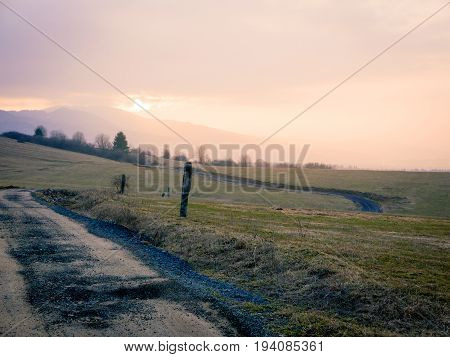 Backcountry dirt road gravel path on foothills of lower tatras mountain in Slovakia at sunset time.