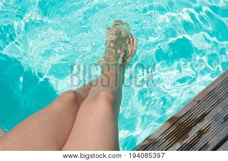 Young Woman's Legs In The Swimming Pool