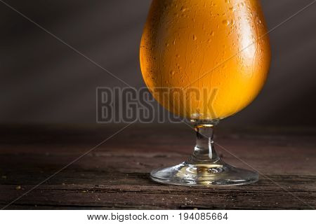 Glass of cold unfiltered light beer on a rustic wooden pub table. Selective focus