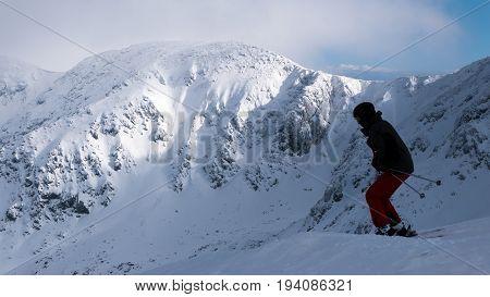 Alone skier ride outside the ski slope.