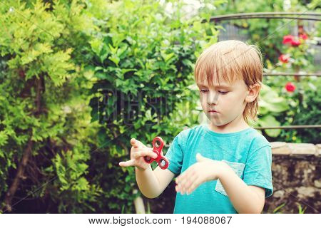 Cute Boy Playing With Tri Fidget Hand Spinner Outdoors. Trendy Toy For Hands For Children And Adults