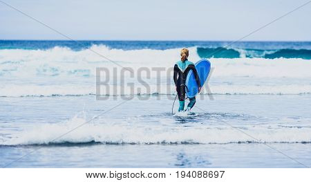Surfer Woman With Surfboard Is Walking And Watching The Waves.
