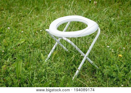 Portable Folding Camp Toilet outdoors in the grass. Camping or motor home toilet accessories for camping in the nature.