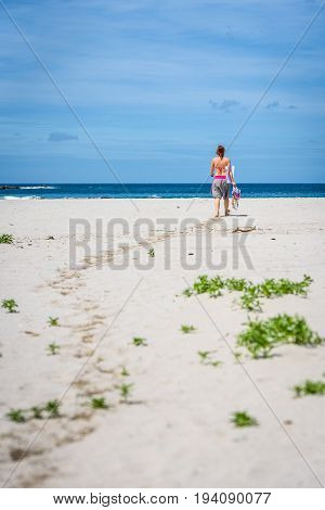 Woman Walking The Beach To Ocean Carrying Towel And Bags.