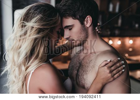Attractive passionate couple on kitchen face to face.