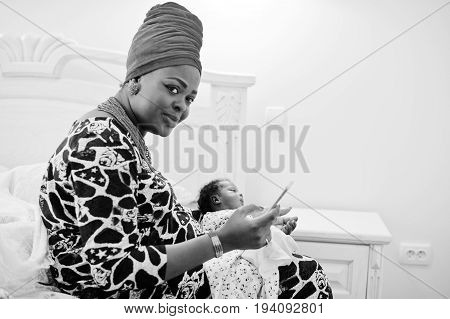 Beautiful Black Woman In Ethnic Clothing Holding Little Baby. Black And White Photo.