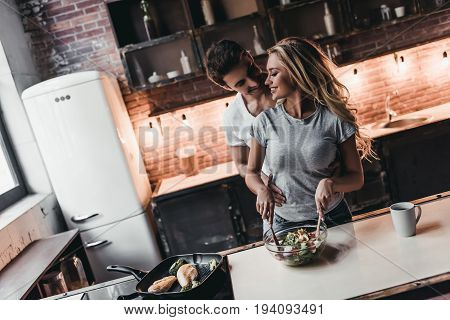 Attractive couple is cooking on kitchen. Salad