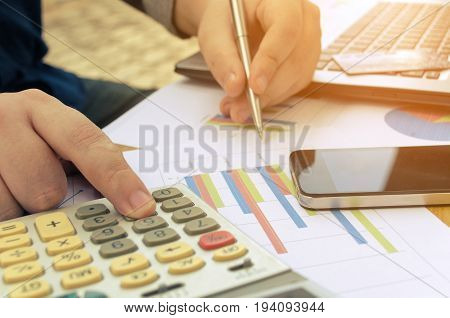 young accountant or business man working and writing with report sheet calculator laptop credit card smartphone finances and calculate on desk savings business economy concept sunlight effect
