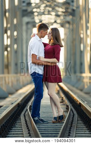 Young man and a girl kissing on railway bridge at sunset. Romantic background