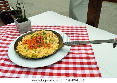 Pasta with cheese and fried onions served in a steel stove at Hofgut Sternen in the Black Forest in Germany
