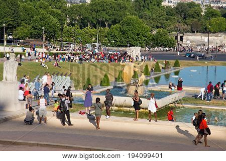 PARIS, FRANCE - JUNE 24, 2017: Unknown people are photographing in the gardens of the Trocadero near the famous Eiffel Tower.