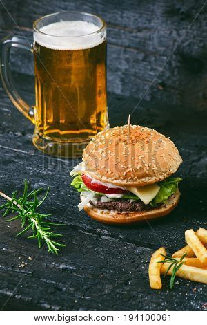 Hamburger with french fries, beer on a burnt, black wooden table. Fast food meal. Homemade hamburger consist of beef meat, lettuce, tomato, bins, dressing, cheese and spices. Vintage