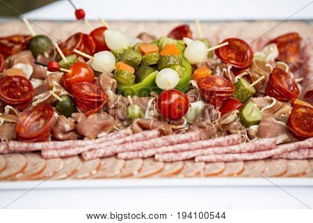 meat appetizer. Plate of charcuterie sausage with vegetables for aperitif time