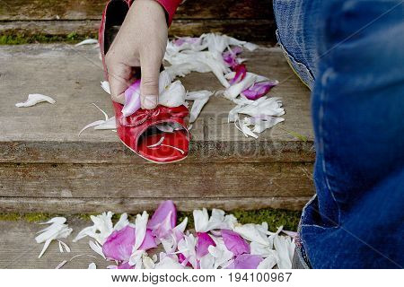 Man sitting on the wooden stairs holding a red shoe scattered with wedding petals. Cropped closeup photo