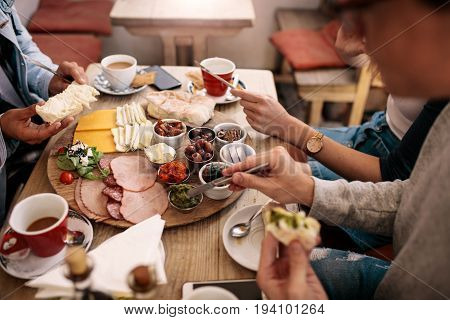 Close up of young people sitting around cafe table and eating with focus on hands and food. Group of students having food in college canteen.