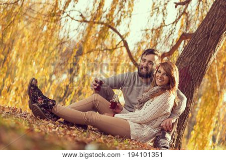 Young couple in love sitting on a fallen autumn leaves under a tree in a park drinking an ice tea and enjoying a wonderful autumn day