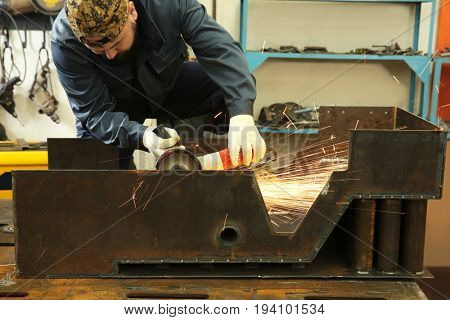 Worker using angle grinder for metalworking in shop