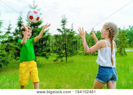 Happy children play with a ball in a summer park.