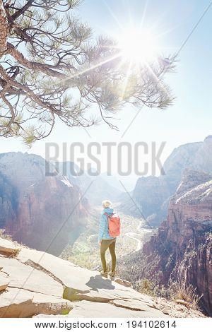 Young female hiker with backpack standing on summit of Angels Landing and enjoying stunning view to Zion Canyon during sunny day, Zion National Park, Utah, USA - hiking and nature lovers concept