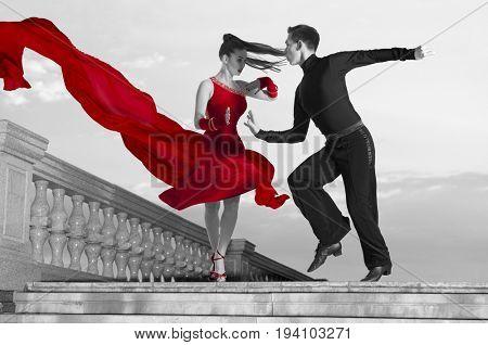 Pair of dancers dancing ballroom on sky background