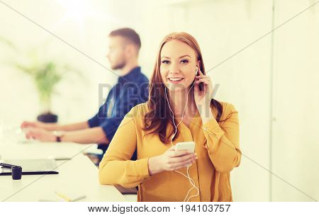 business, startup, technology and people concept - happy businesswoman or creative worker with earphones listening to music on smartphone at office