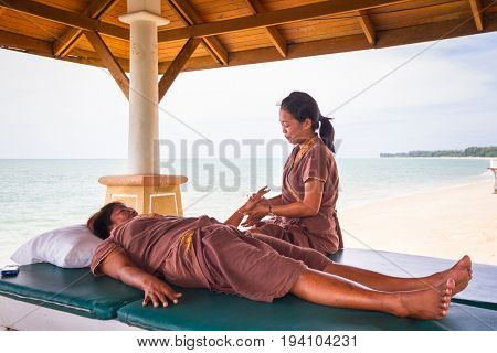 KOH KHO KHAO, THAILAND - NOVEMBER 10, 2012: Thai masseuses on the tropical beach of Koh Kho Khao island in Thailand. Thai massage is an ancient healing system.