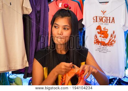 KHAO LAK, THAILAND - NOVEMBER 5, 2012: Beautiful Thai woman selling T-shirts on the local market in Khao Lak, Thailand. This market is also tourist attraction in Phang Nga province.