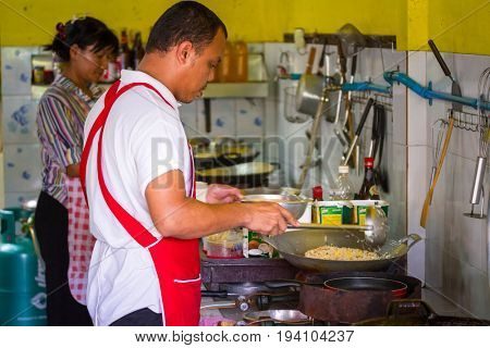 KOH KHO KHAO, THAILAND - NOVEMBER 10, 2012: Man making traditional pad thai in open kitchen of Koh Kho Khao, Thailand. Pad Thai is a traditional meal in Thailand.