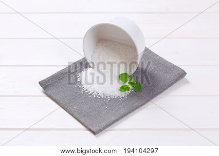 bowl of coarse grained sea salt spilt out on grey place mat
