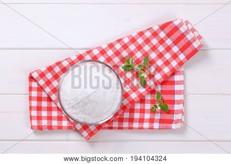 bowl of coarse grained sea salt on checkered dishtowel